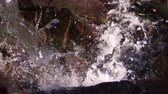 summer : Shot from top view of waterfall as it splashes downward. Rock is visible. Slow motion.