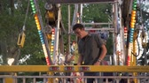 piscando : A shot of two people exiting a ferris wheel ride at a carnival. The boy holds the exit door open for the girl