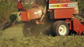 技術 : Medium shot of a square hay baler. The camera moves from left to right as it follows the movements of the baler.
