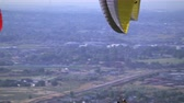 paragliding : Two people are paragliding together one in front of the other with one parachute. They pass by another paraglider. Valley and highway can be seen below.