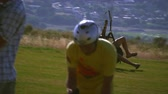 salt : A man who is paragliding is coming in for a landing on the grassy hill. He slows himself down by brushing the ground then he is able to stop. He is at the Point of the mountain in South Salt Lake valley UT. Stock Footage