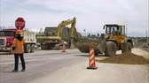 tabela : Static shot of a bulldozer picking up a load of dirt and backing away as a man holding a stop sign watches.
