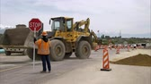 技術 : Static shot of a bulldozer picking up a load of dirt and backing away as a man holding a stop sign watches.