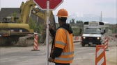 ustabaşı : Tilt of a African-American man holding a stop sign at a highway construction site.