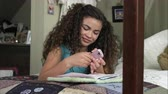 poste : Slow motion of girl writing in diary on her bed then texting.