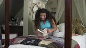 poste : Slow motion of girl reading book while lying across her bed.