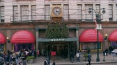 тент : Shot from the street of Macys department store entrance with christmas lights and trees. People are walking on sidewalk carrying bags and wearing coats and hats.
