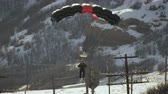 padák : Slow motion footage of a parachute-wearing skiier landing on a snowy mountain slope.