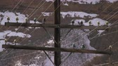 wintertime : Static shot of power lines. Snow covered montains are visible in the background.