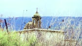 vinha : An old Maronite Christian church,topped with a cross. Racked focus to a bird that just came to light on a barren twig in the foreground,near the palace of Agrippa in Banias,Golan Heights,Israel. Shot with the Red One digital camera at 4k 4096 x 2304 resol