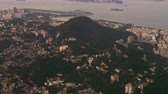 atravessar : Aerial pan of Rio de Janeiro, the Atlantic Ocean, and urban sprawl. Boats pass through the horizon of the footage while the camera pans across the varying neighborhoods of Rio.