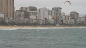 surfe : Shot of group of five different parasailing surfers distance from shore. City skyscrapers are in the background. beach is sandy Looks like fun. Filmed during the day. Vídeos