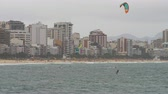 surfe : Parasailing surfer is distance form beach. He eventualley goes under. Parachute is brightly colored, green, red and blue. Cityscape is in background.