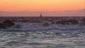 veneza : Slow motion view of sailboat on the horizon at sunset.