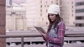 技術 : View of woman in hat swiping on tablet standing outside.