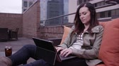 relaxation : Woman relaxing on roof top adjusting laptop and typing.