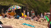 volný čas : Close shot of clear Hawaii beach dotted with people resting and preparing to swim with green mountain and rock ledge in background Dostupné videozáznamy