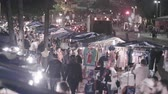 nagy : Static shot of tee shirt street vendors crowded along busy street. T-shirts are hanging in stalls. Big truck is driving in the street. Filmed at night. Couples and people are shopping. Stock mozgókép
