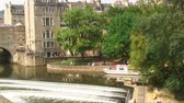 pilíř : View of the Pulteney Weir and bridge with a ferry on the River Avon. Also showing green trees and stone buildings of Bath, England.