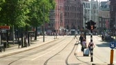commute : Tram tracks in Amsterdam, the Netherlands. Two women walk by with a suitcase. Stock Footage