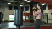 walka : Woman in a gym practicing her punching and kicking moves on a freestanding punching and kicking bag
