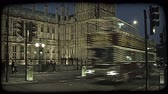 político : English double decker buses, cars, and people crossing the lit street adjoining the English Parliament in London, England at dusk. Vintage stylized video clip.