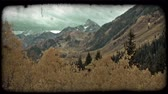 сосна : Pan, left to right, of mountainous valley overlook with tall brown mountains in distance and large evergreen pine trees in foreground over to slope of mountain, covered with evergreen trees and other mountain trees full of autumn color. Vintage stylized v