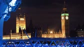 britânico : Time-lapse of Big Ben and the Houses of Parliament at night with the London Eye ferris wheel, illuminated with blue light, in the foreground. Filmed in October 2011. Panning shot.