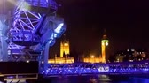 britânico : Time-lapse of the London Eye with Big Ben and the Houses of Parliament in the background. Filmed at night when the Ferris wheel is lit in purple and blue light. Filmed in October 2011. Cropped.