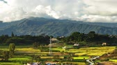 Time-lapse of the countryside of Nepal with changing light and billowing clouds over mountains. The valley floor is covered in fields with a few buildings. Panning shot. Stock Footage
