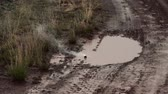 lamacento : A training explosive is thrown into a muddy puddle on the side of a dirt road. It lets out smoke and then explodes. From a training for Green Beret United States Army Special Forces.