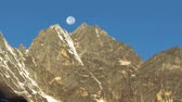 Time-lapse of the moon going behind Himalayan peaks in the morning. Shadows advance as the sun rises. Cropped. Stok Video