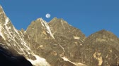 Time-lapse of the moon going behind Himalayan peaks in the morning. Shadows advance as the sun rises. Panning shot.
