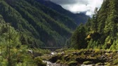 Time-lapse of a river and a trail in a Himalayan valley. People and animals pass by on the trail as clouds pass over the green, forested valley walls. Cropped.