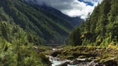 Time-lapse of a river and a trail in a Himalayan valley. People and animals pass by on the trail as clouds pass over the green, forested valley walls. Panning shot.
