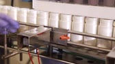 parte : Tracking shot of a a factory filling station with plastic bottles on a conveyor belt and a blue gloved hand moving them along. Vídeos