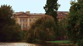 nobre : Stationary shot of Buckingham Palace in the background filmed from Saint James Park. There are plenty of trees, a waterway and some people walking in the park. Captured on October 8, 2011. Stock Footage