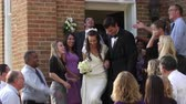 clap : Slow-motion shot of a bride and groom walking out of a church door and down steps as guests throw rice above them and applaud. Stock Footage