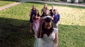 empregada : Slow-motion shot of a bride throwing her bouquet of flowers over her head to a group of girls. One catches it and they all cheer.