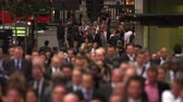 caminhada : Businesspeople are commuting home after the end of their workday in London. They are walking down a crowded street. on the left some street traffic - cars taxis double-decker a group of cyclists - can be seen. People closer to the camera are blurred. Film Stock Footage