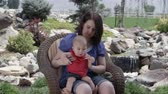 smiling girl : Slow motion of woman sitting baby girl down in her lap while sitting in chair outside.
