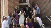 confete : A bride and groom walk out of a church door and down steps as guests throw rice above them and applaud.