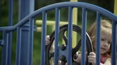 smiling girl : Slow motion rack focus of red headed girl play on playground and steering wheel. Stock Footage