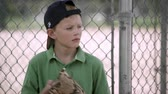 dospívající : Slow motion of boy looking to the side as he hits his baseball mitt. Dostupné videozáznamy