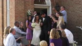 clap : A bride and groom walk out of a church door and down steps as guests throw rice above them and applaud.