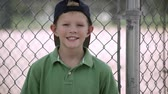 capô : Slow motion of boy hitting baseball mitt as he turns and smiles. Stock Footage