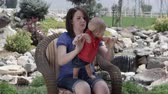 smiling girl : Slow motion of woman holding baby girl standing on her lap outside near a waterfall.