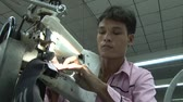 sítí : Male garment factory worker places dark heavy fabric strips into heavy industrial sewing machine