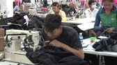 sítí : Male garment worker sewing jeans at his machine with great speed