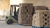 sítí : Forklift and unidentified driver idling among stack of boxes and pallets at the loading bay of garment factory